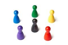 Seis figuras do jogo que estão em um círculo com uma figura preta no meio Símbolo para uma roda de cor ou um grupo de pessoas Foto de Stock