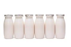 Seis frascos plásticos com o leite isolado imagens de stock