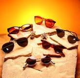 Seis gafas de sol sobre la arena y piedras fotografía de archivo libre de regalías