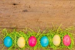 Seis huevos coloreados con los greass de Pascua en la madera del granero imagenes de archivo