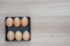 Seis huevos en placa negra en superficie de madera con el espacio para el texto Foto de archivo