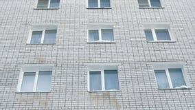 Seis janelas brancas de uma casa do tijolo Vista exterior da construção Movimento da câmera de cima para baixo filme