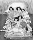 Seis jovens mulheres de sorriso que encontram-se em uma cama (todas as pessoas descritas não são umas vivas mais longo e nenhuma  Fotografia de Stock