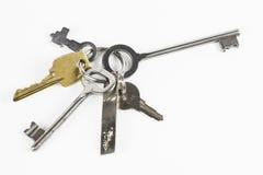 Seis llaves del metal de diversa forma en el fondo blanco Foto de archivo