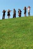Seis músicos jogam violinos de encontro ao céu Imagens de Stock Royalty Free