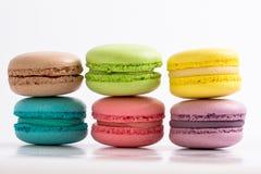 Seis macarons franceses coloridos en el fondo blanco, mintiendo en el top Fotografía de archivo