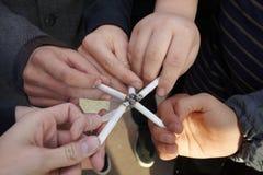 Seis manos de adolescencias con los cigarrillos se cierran cerca Foto de archivo libre de regalías