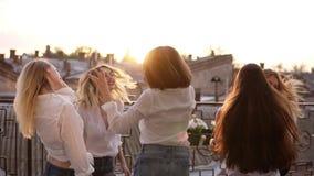 Seis mujeres están colgando hacia fuera juntas en la terraza Todos en la misma ropa del estilo BAILE y SALTO Ropa casual almacen de metraje de vídeo