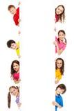 Seis niños que miran de la cartelera en blanco Fotografía de archivo libre de regalías