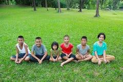 Seis niños que juegan en el parque Imagen de archivo