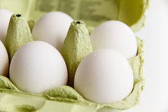 Seis ovos brancos em um pacote verde aberto Imagem de Stock