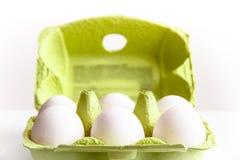 Seis ovos brancos em um pacote verde aberto Fotos de Stock