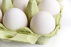 Seis ovos brancos em um pacote verde aberto, visto da parte superior Fotografia de Stock Royalty Free