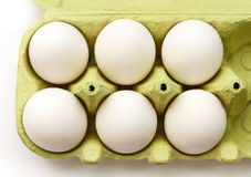 Seis ovos brancos em um pacote verde aberto, visto da parte superior Fotos de Stock Royalty Free
