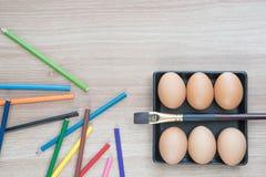 Seis ovos na placa do quadrado preto com uma escova e os lápis da cor Foto de Stock Royalty Free