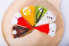 Seis partes de bolo do fruto na placa de madeira Imagens de Stock Royalty Free