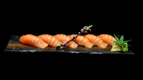 Seis pedazos de sushi de color salmón fijaron en la placa de cerámica de madera con Estilo japonés de la comida de la tradición Fotografía de archivo