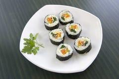 Seis pedazos de sushi y de una hoja del perejil. Fotografía de archivo libre de regalías