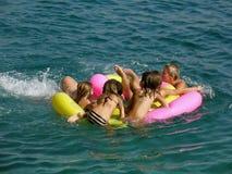 Seis personas en la muchedumbre en la playa juegan en el mar Imagenes de archivo