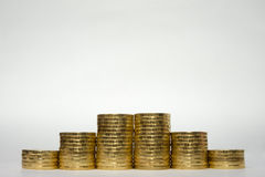 Seis pilas de monedas que aumentan altura simétricamente en un fondo blanco, soportes cacarañados al borde del ruso 10 rublos Imagen de archivo libre de regalías