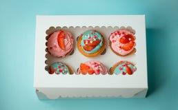 Seis queques coloridos decorados com polvilham e morangos Foto de Stock