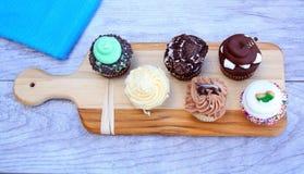 Seis queques na placa de corte no fundo de madeira Fotografia de Stock Royalty Free