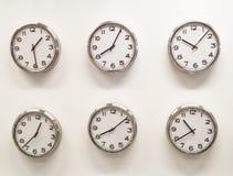 Seis relojes en la pared blanca Foto de archivo libre de regalías