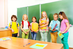 Seis suportes das crianças na fileira perto do quadro-negro Fotografia de Stock Royalty Free
