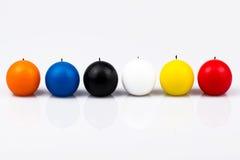 Seis velas coloreadas en un fondo blanco Imagenes de archivo