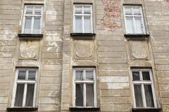 Seis ventanas blancas del vintage en la fachada de la casa vieja desigual Imagen de archivo