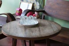 Seis vidrios en la bandeja blanca pusieron el lado abajo en la tabla de madera con el na Imágenes de archivo libres de regalías