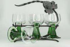 Seis vidros de vinho com as hastes verdes que sentam-se em um ferro forjado submetem fotografia de stock royalty free