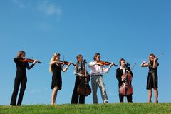 Seis violines del juego de los músicos contra el cielo Fotos de archivo libres de regalías