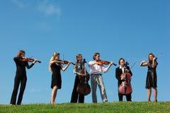 Seis violinos do jogo dos músicos de encontro ao céu Fotos de Stock Royalty Free