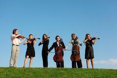 Seis violinos do jogo dos músicos de encontro ao céu Fotos de Stock