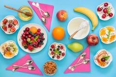 Seis yogures e ingredientes diferentemente vestidos Imagen de archivo