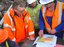 Seismic discussion. Geologists discuss the oil-bearing formation being explored in a seismic reflective survey on the West Coast of New Zealand Royalty Free Stock Photo