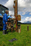Seismic testing. A man uses a fence post driver to generate sound waves through the ground in an electro-seismic survey for well water. This method can also be Royalty Free Stock Photography