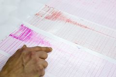 Seismological activity lines human hand. Seismological activity lines on the sheet of measuring paper. Seismological device for measuring earthquakes. Earthquake royalty free stock images