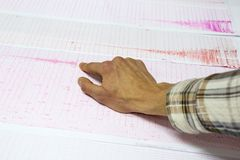 Seismological activity lines human hand. Seismological activity lines on the sheet of measuring paper. Seismological device for measuring earthquakes. Earthquake stock photo