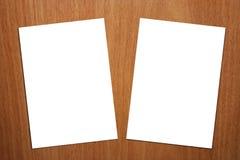 Seite 2 weiße A4 auf hölzernem Hintergrund - Version 2 Stockfotografie
