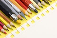 Seite des leeren Papiers und bunte Bleistifte auf gelbem Hintergrund Lizenzfreie Stockfotos