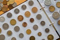 Seite des Münzkundealbums mit verschiedenen Münzen lizenzfreie stockbilder