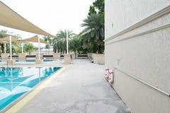 Seite des Swimmingpools mit Gebäude mit Rettungsringen oder Rettungsring stockfotos