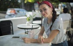 Seiten-auf Schuss einer jungen Frau in der legeren Kleidung, die im offenen Café sitzt, lizenzfreies stockfoto