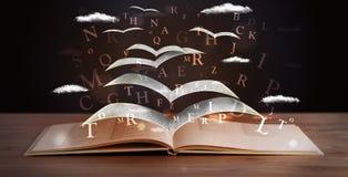 Seiten und glühende Buchstaben, die aus einem Buch heraus fliegen Stockfotos