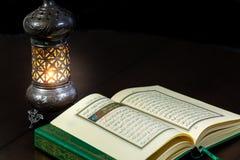 Seiten von Qur-` der Heiligen Schrift, das mit Weinleselampe ist Stockfotografie