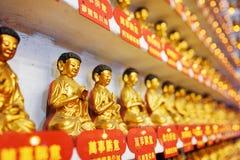Seitenansicht über verschiedene kleine goldene Buddha-Statuen im interi Stockfotos