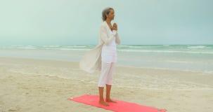 Seitenansicht der aktiven älteren Afroamerikanerfrau, die Yoga auf Übungsmatte am Strand 4k tut stock video footage