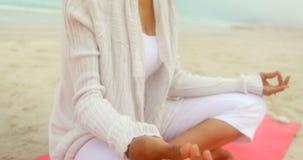 Seitenansicht der aktiven älteren Afroamerikanerfrau, die Yoga auf Übungsmatte am Strand 4k tut stock footage